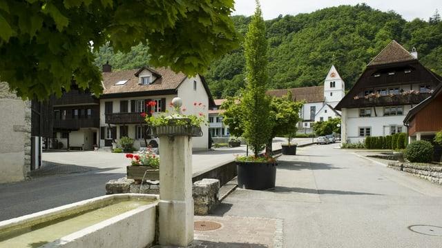 Brunnen an einer Strasse in einem Dorf.