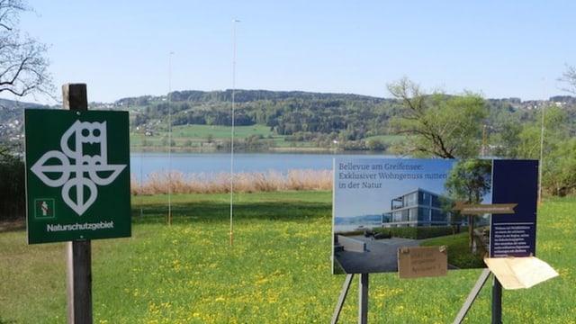 Vor einem See stehen zwei Tafeln am Ufer. Eines zeigt das Symbol des Naturschutz, daneben wirbt ein Plakat für Luxuswohnungen.