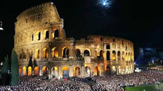 Grosse Menschenmenge versammelt sich in der Nacht vor dem hell erleuchteten Kolosseum.