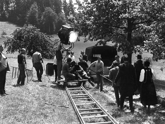 Kamerafahrt auf Schienen entlang eines Feldweges. Eine Schauspielerin und ein Schauspieler gehen den Weg entlang. Auf dem Kamerawagen steht ausserdem ein grosser Filmscheinwerfer.