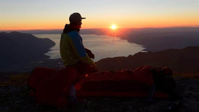 Mann, der den Sonnenuntegang über dem Genfersee beobachtet