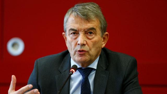 Wolfgang Niersbach in einem Anzug vor einem roten Hintergrund