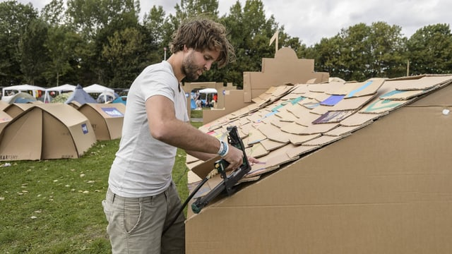Ein Mann befestigt ein Kartent an einem Festival
