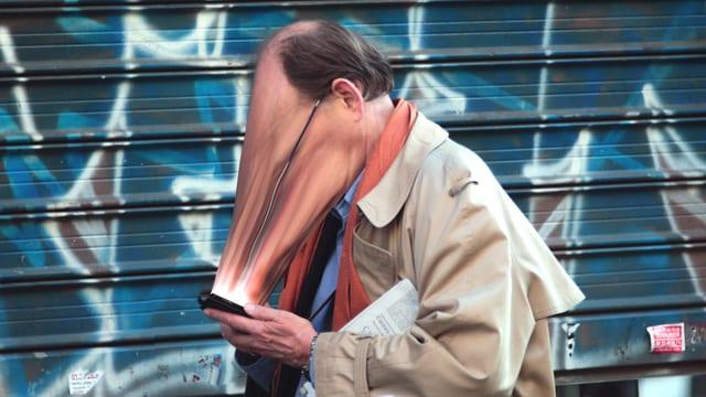 Ein Mann mit zum Smartphone hin verzerrtem Gesicht.