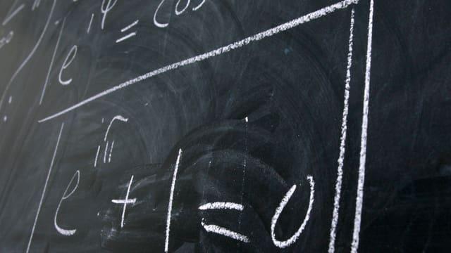 Eine Wandtafel mit mathematischen Formeln beschrieben.