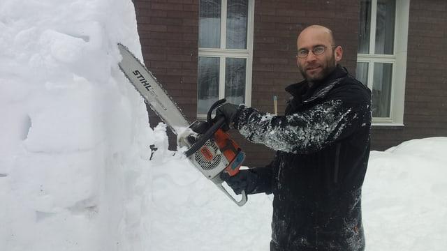 Roger Leu mit einer Motorsäge vor einer Schneewand.
