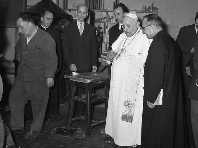Der Papst in weisser Kutte auf einem schwarz-weiss-Bild, besucht 1959 die Mitarbeiter der Vatikanzeitschrift. Er ist umgeben von Mitarbeiternm, die ihn willkommen heissen.