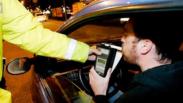 Ein Mann hinter dem Steuer eines Autos bläst auf Geheiss eines Polizisten in ein Promille-Testgerät