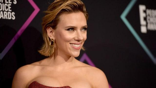 Scarlett Johansson seitlich fotografiert lächelt den Fotografen zu.