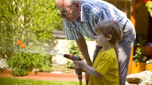 Ein älterer Herr steht neben einem Knaben, der mit einem Schlauch den Garten wässert.