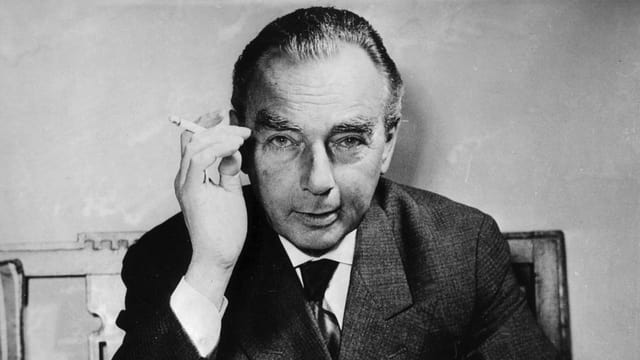 Poträtfoto von Erich Kästner, der direkt in die Kamera schaut. In seiner rechten Hand eine Zigarette.