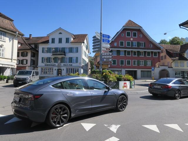Auto in einem Kreisel, historische Häuser im Hintergrund.