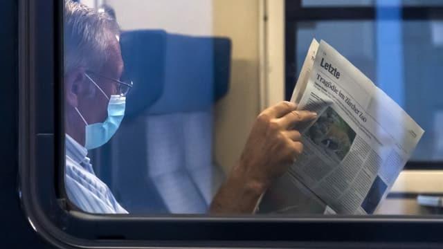 um cun mascra legia gasetta en il tren.