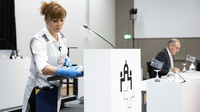 Eine Frau trägt Schutzhandschuhe und desinfiziert ein Rednerpult.