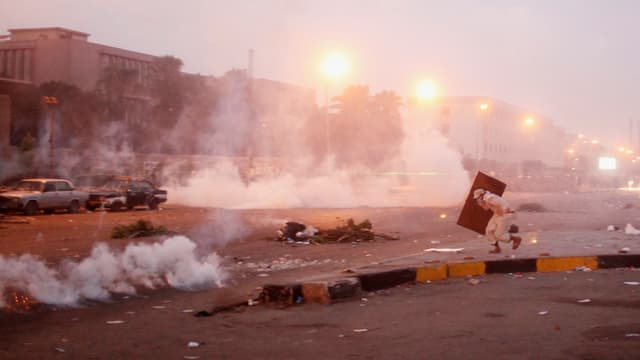 Eine Strasse im Morgengrauen, Schwaden von Tränengas. Ein Mann mit Schild rennt gebückt über die Strasse.