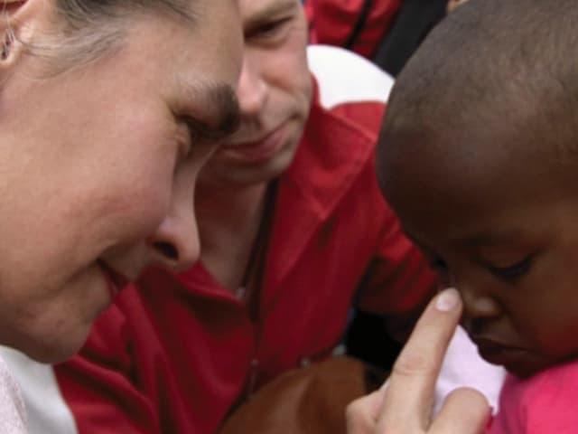 Frau und Mann knien vor Kind, sie stupst mit dem Finger seine Nase.
