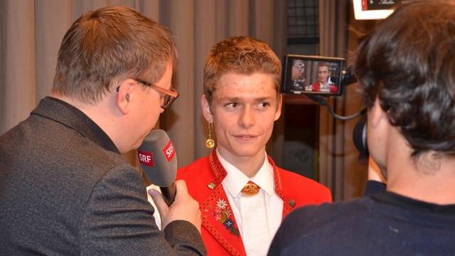 Ein junger Mann in Appenzeller Tracht während eines Interviews.