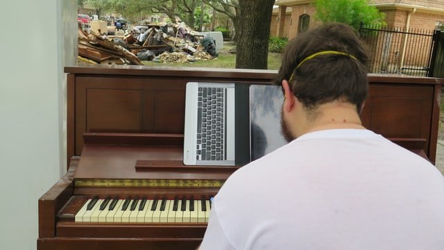 Ein Mann spielt Klavier - mit Gummihandschuhen und Mundschutz.
