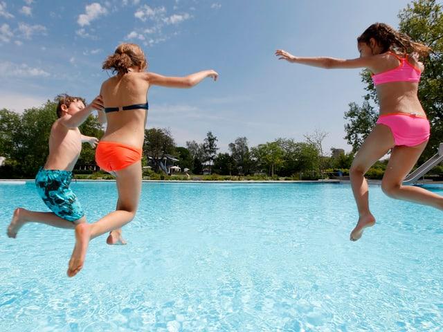 Drei Kinder springen in ein Schwimmbad.