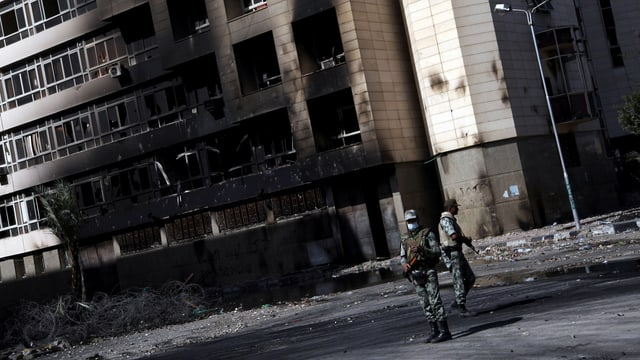 Zwei Soldaten vor einem abgebrannten Hochhaus.