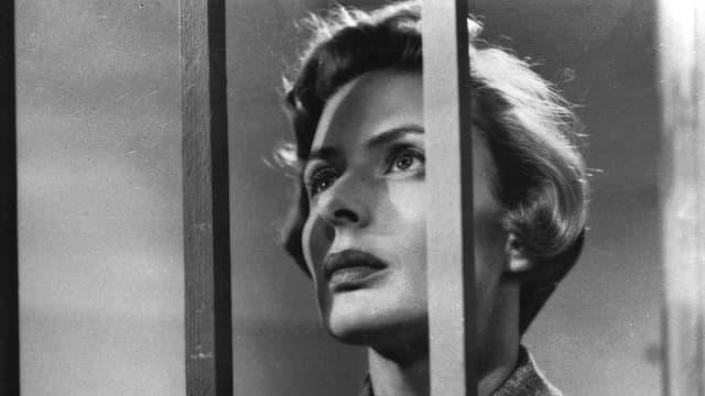 Ingrid Bergman hinter Gitterstäben, nach oben schauend.