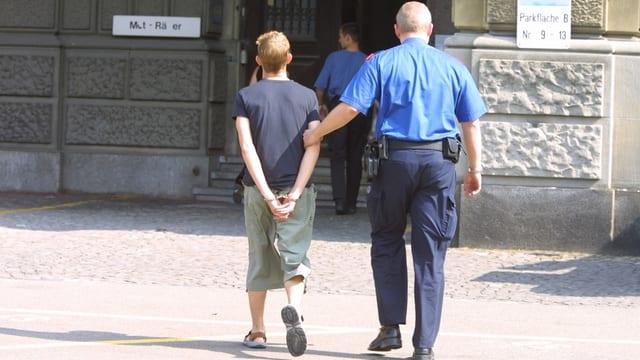 Polizist führt einen Jugendlichen in Handschellen zum Gerichtsgebäude