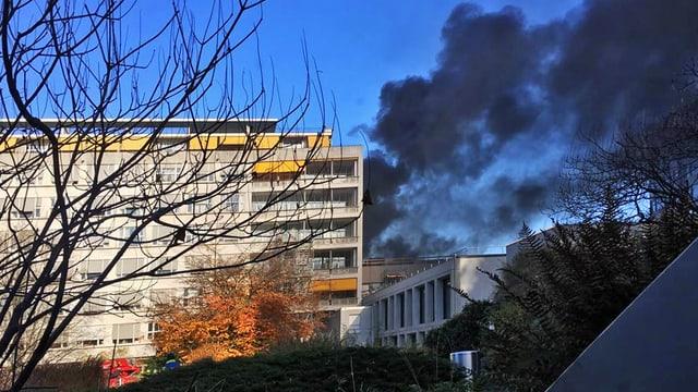 dicke schwarze Rauchwolke über dem Spital