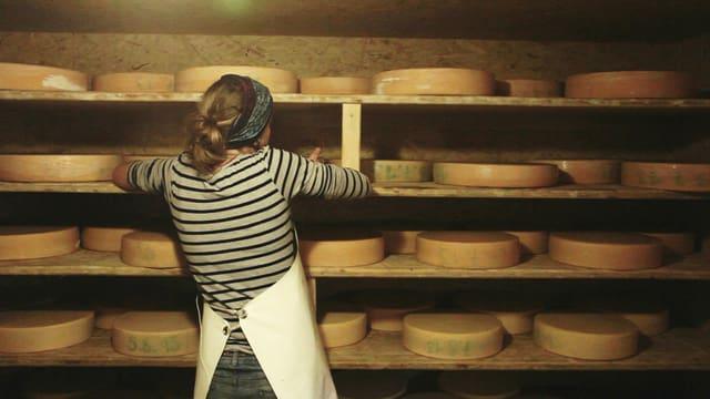 Frau stellt Käse ins Regal