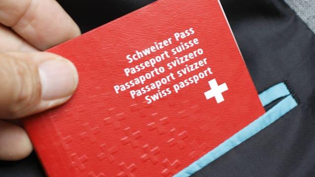 Eine Hand zieht einen Schweizer Pass aus einer Vestontasche.