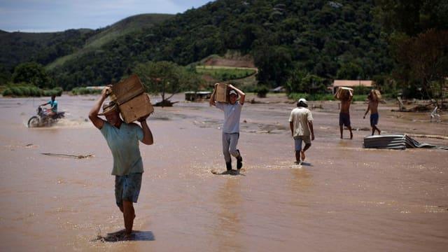 Persunas che cumbattan cunter las inundaziuns.