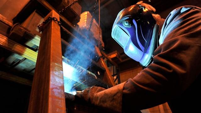 Ein Arbeiter mit Gesichtsmaske schweist ein Treppenteil.