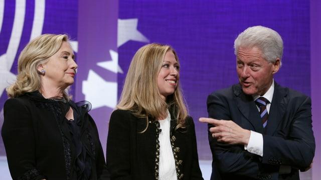 Hillary, Chelsea und Bill Clinton stehen auf einer Bühne.