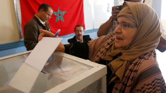 Frau wirft Zettel in Wahlurne.
