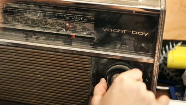 Ein altes, leicht schmutziges Radio, eine Hand dreht am Regler.