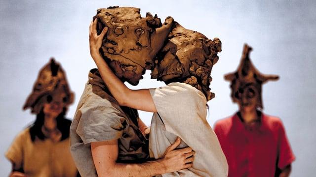 Zwei Tänzer mit Masken aus Ton küssen sich.