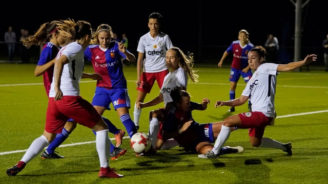 Je vier Spielerinnen - die einen in Blau-Rot, die anderen in Rot-Weiss - kämpfen um den Ball.