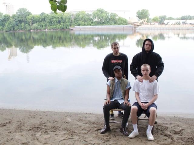 Zwei junge Männer sitzen auf Stühlen nebeneinander an einem Baggersee, hinter ihnen stehen zwei weitere junge Männer