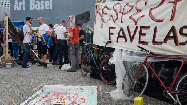 Transparent, dahinter diskutierende Leute und im Hintergrund das Logo der Art.
