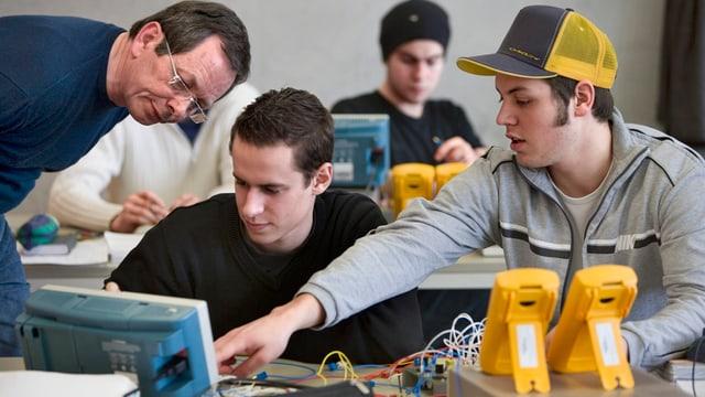 Junge Männer in der Berufsschule mit allerlei technisch-elektronischem Gerät auf dem Tisch.
