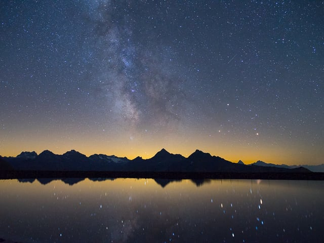 Ein See, Bergpanorama und Sternenhimmel.