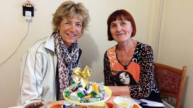 Zwei Frauen sitzen am Tisch und trinken Tee zusammen.