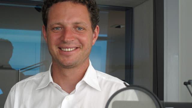 Samuel Vörös steht hinter einem Mikrofon im Radiostudio.