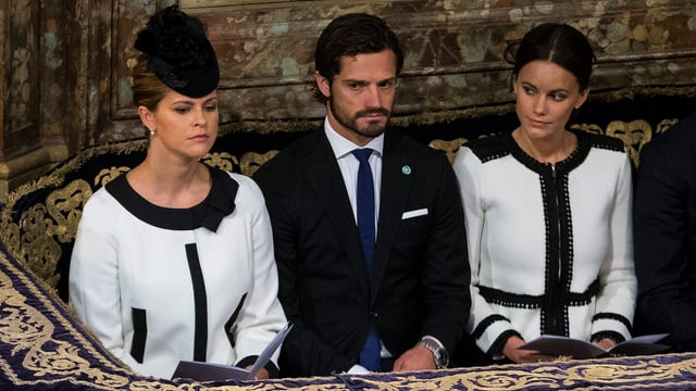 Prinzessin Madeleine und Prinzessin Sofia sitzen in einem ähnlichen schwarz-weissen Kleid im Parlament von Schweden. Dazwischen ist Prinz Carl Philipp.