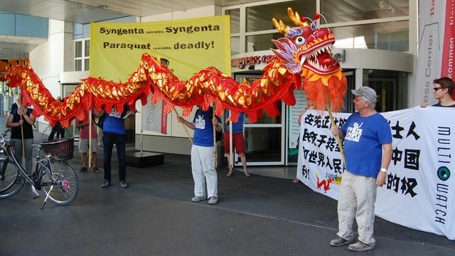 Protestierende halten einen chinesischen Drachen in der Hand, Transparente im Hintergrund.