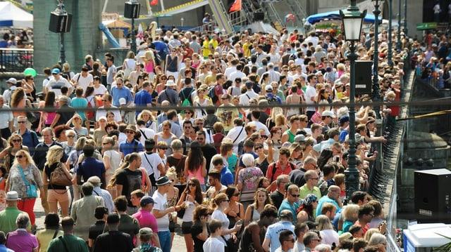 Eine grosse Menschenmenge drängt sich über eine Brücke.