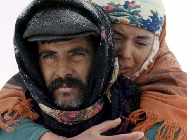 FIlmstill: Ein Mann trägt eine Frau auf dem Rücken.