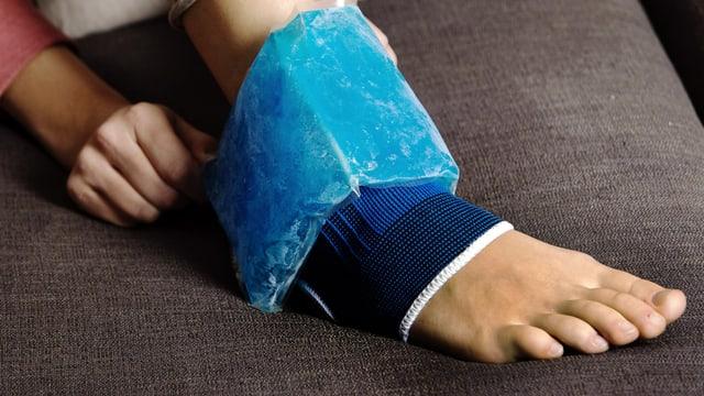 Verstauchter Fuss mit Bandage und Kühlmanschette auf Sofa.