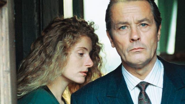 Eine blonde Frau mit Locken und ein Mann in Anzug und Krawatte.