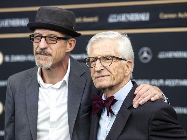 Ein Mann mittleren Alters und ein älterer Mann stehen Arm in Arm vor Kameras.