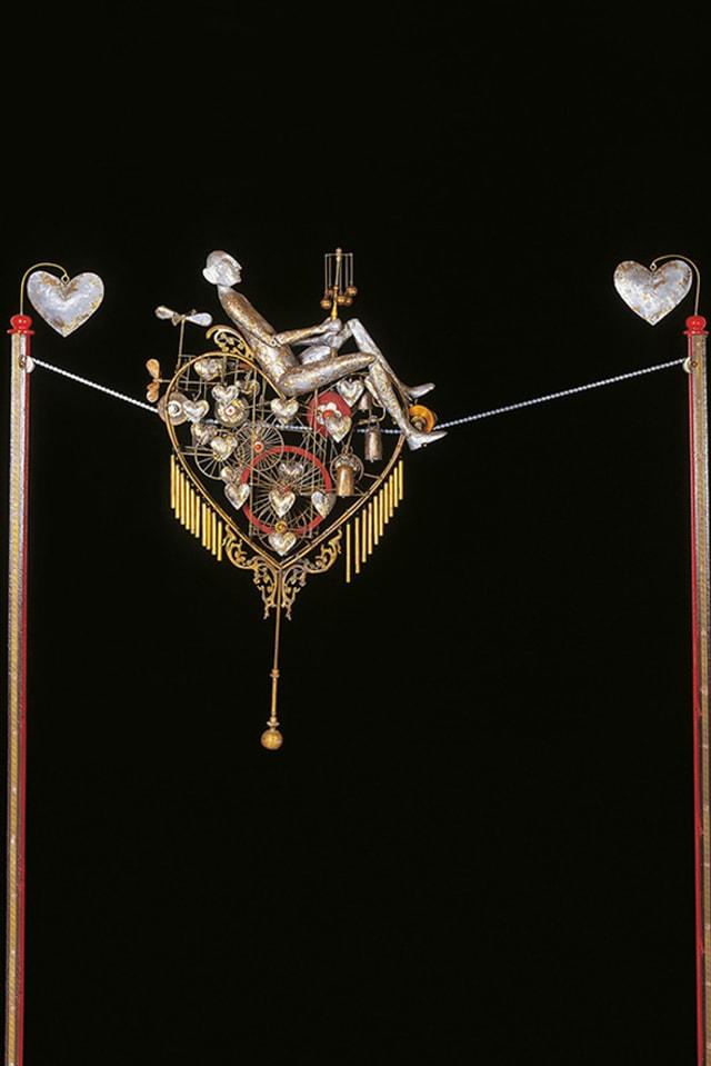 Skulptur einer Figur, die zwischen zwei Herzen in einer herzförmigen Seilbahn fährt.